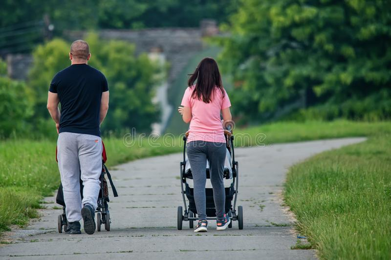 A young couple pushing a baby carriage royalty free stock photo