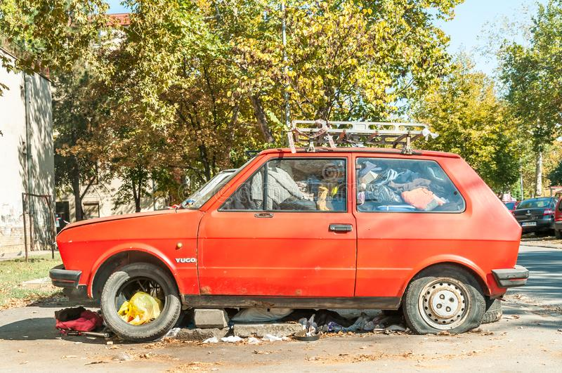 Novi Sad, Serbia. 05 - October 2018. Old rusty red broken and damaged Yugo car full of junk parked and abandoned on the street. Ed. Old rusty red broken and royalty free stock images