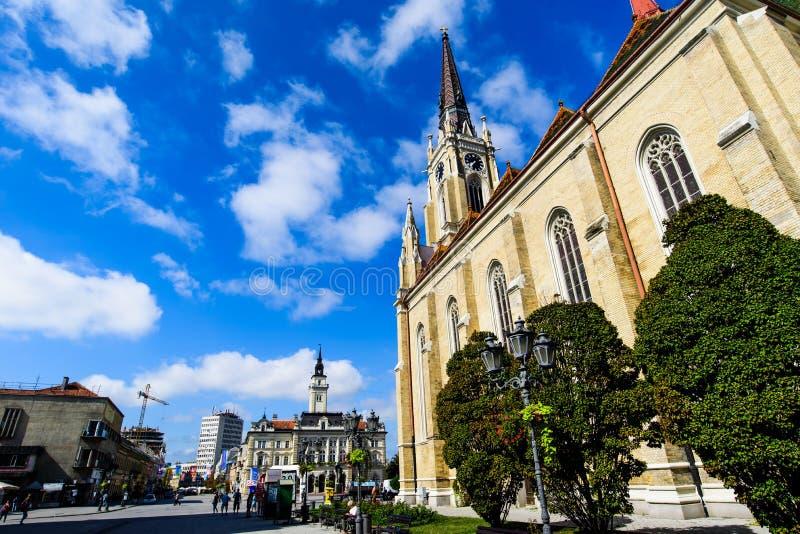 Novi Sad Serbien - Augusti 15, 2018: Novi Sad domkyrka och fot- gå områdessikt på fyrkanten för central stad på en solig dag arkivfoto