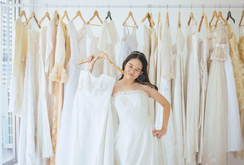 Novia adolescente asiática que intenta en el vestido de boda, diseñador de la mujer que hace el ajuste en casarse la tienda de ro imagenes de archivo