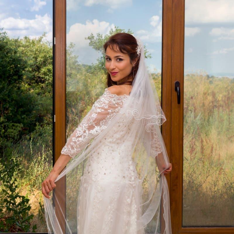 Novia alegre delante de la ventana fotos de archivo