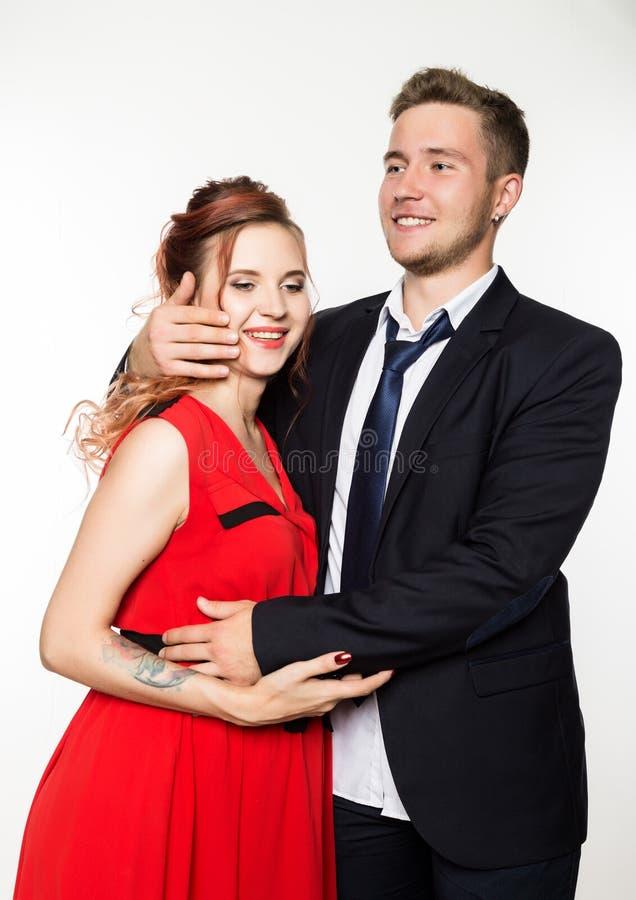 Novia alegre y novio embarazadas que se unen en un fondo blanco imagenes de archivo