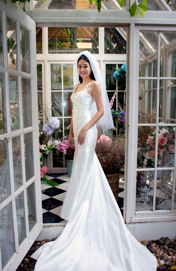 Novia asiática en un vestido blanco con en el invernadero el ramo de fondo de las flores imagen de archivo libre de regalías