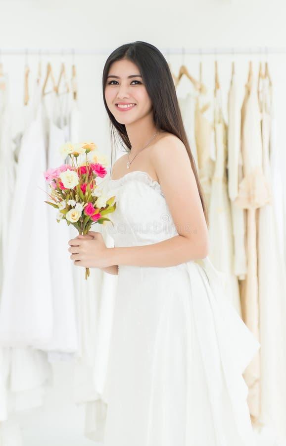Novia asiática hermosa de la mujer en la flor blanca y la sonrisa de la tenencia del vestido que se casa foto de archivo
