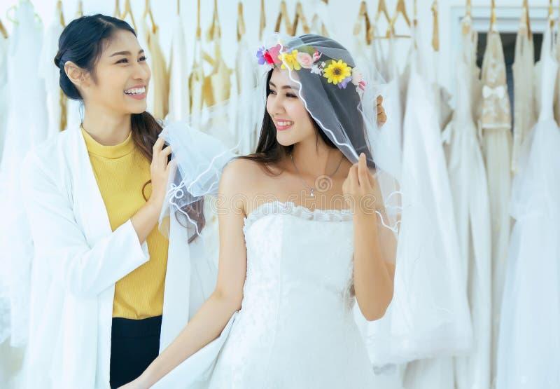 Novia asiática que intenta en el vestido de boda, el diseñador de la mujer que hace el ajuste, feliz y la sonrisa fotografía de archivo libre de regalías