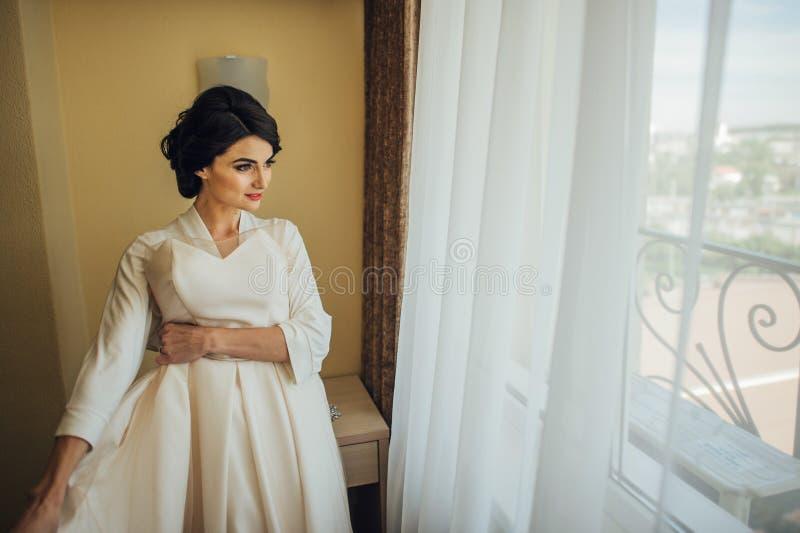 Novia atractiva hermosa en el vestido blanco que presenta debajo de la cortina imagen de archivo libre de regalías