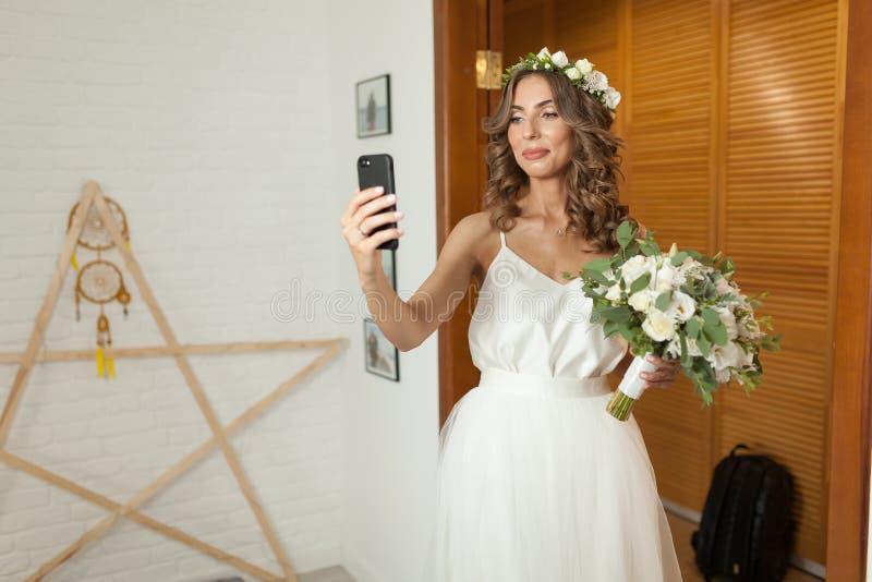 Novia caucásica romántica y feliz en el vestido de boda elegante que toma el selfie en el fondo del sitio hermoso imagen de archivo