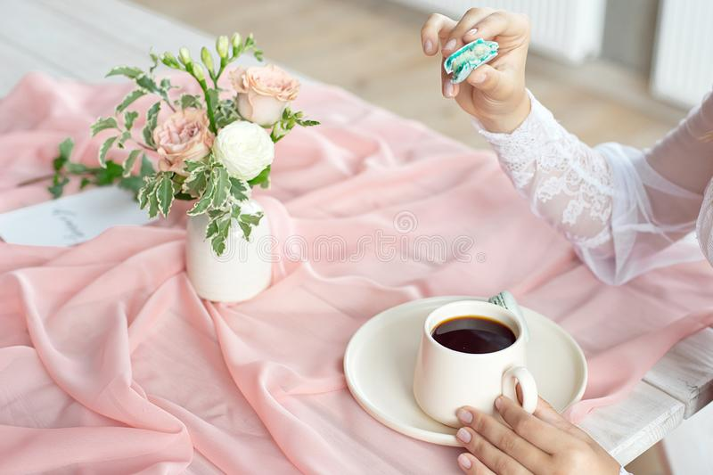 Novia cauc?sica hermosa joven que goza del desayuno de los macarrones y del caf? franceses en una tabla de madera con un rosa de  fotografía de archivo