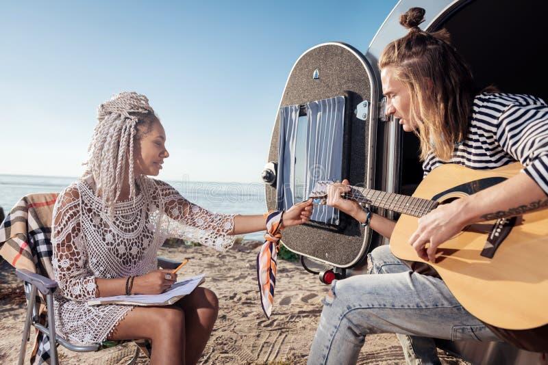 Novia con los dreadlocks blancos que adaptan la guitarra para su novio fotos de archivo