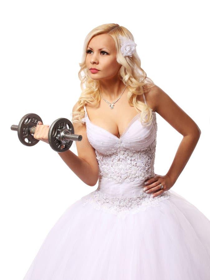 Novia con pesa de gimnasia. mujer joven rubia hermosa en el vestido de boda aislado imagenes de archivo