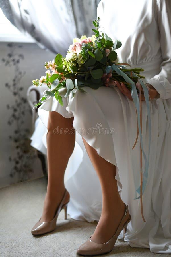Novia con un ramo delante de la ventana que espera al novio imagen de archivo