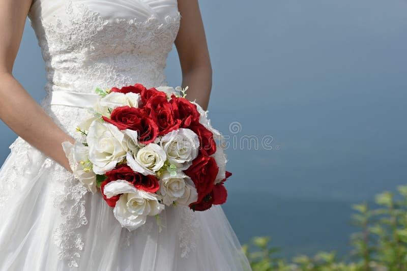 Novia cosechada del tiro que sostiene una broche de la flor en pre casarse el tiro imagen de archivo libre de regalías