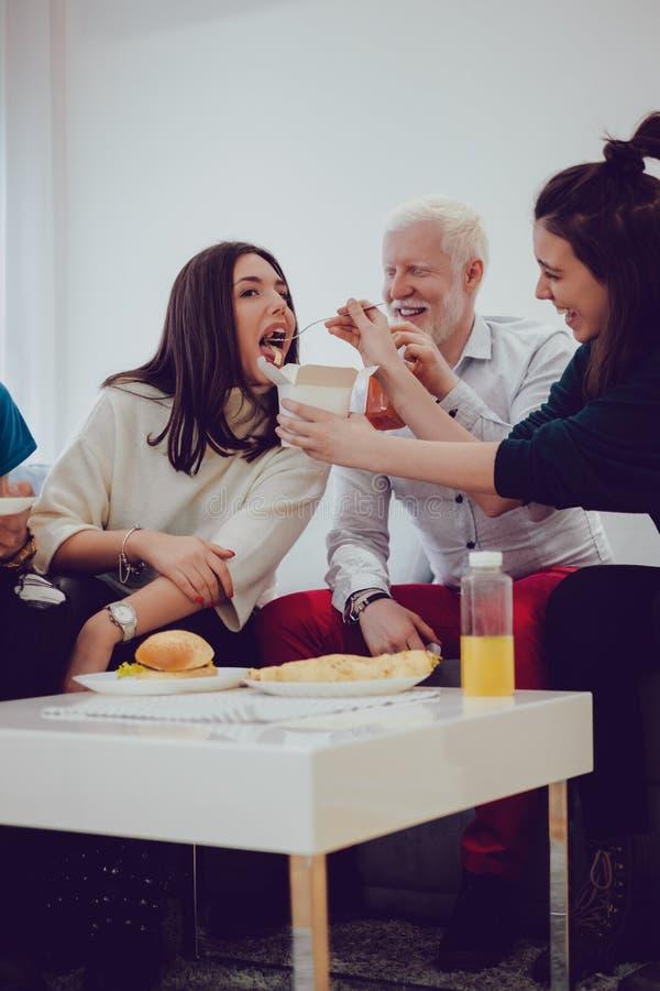 Novia de alimentación de la muchacha con las pastas mientras que están sonriendo los amigos imagenes de archivo