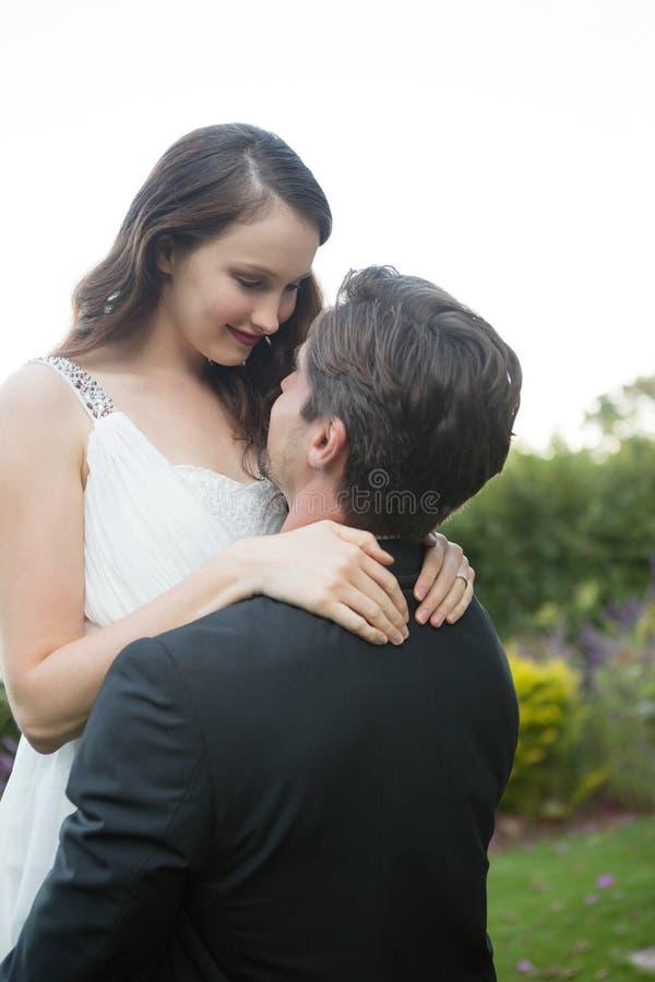 Novia de elevación del novio romántico mientras que se coloca en parque imagen de archivo libre de regalías