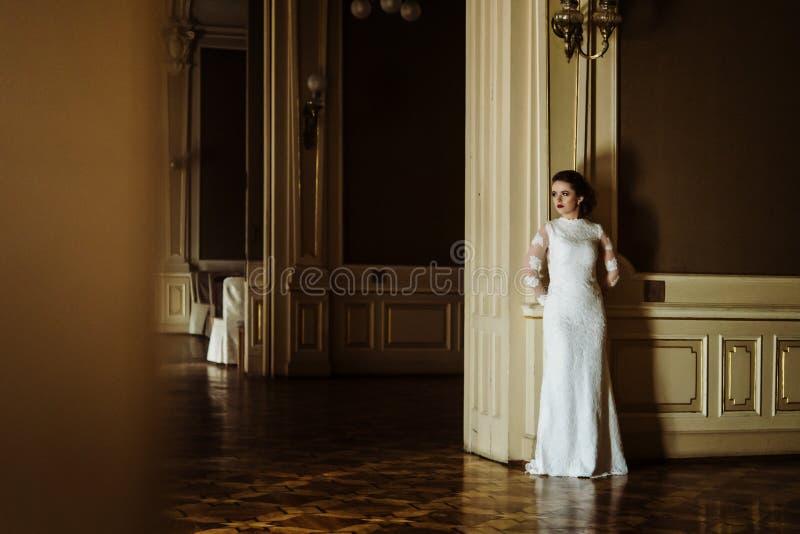Novia de lujo elegante que presenta en el fondo del interior rico foto de archivo libre de regalías