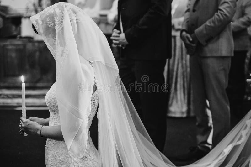 Novia debajo del velo que ruega con la luz de la vela Pares elegantes felices de la boda que llevan a cabo velas durante matrimon fotografía de archivo