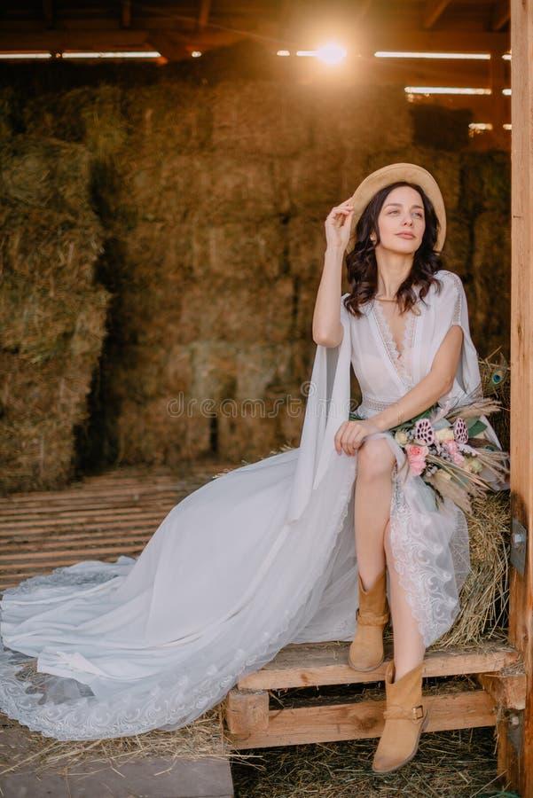 Novia del estilo de Boho que se sienta cerca del henil en rancho foto de archivo libre de regalías