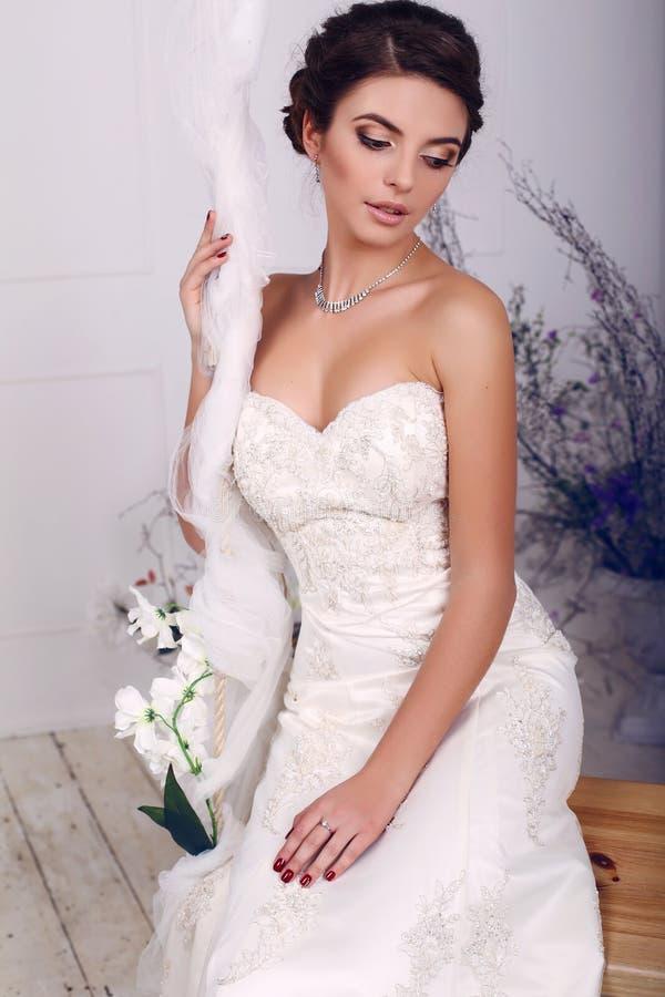 Novia elegante hermosa en el vestido de boda que se sienta en el oscilación fotografía de archivo