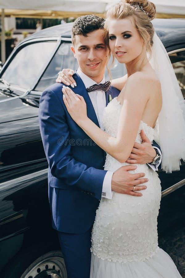 Novia elegante y novio felices que presentan en el coche retro viejo Pares magníficos de la boda de los recienes casados que sonr imagen de archivo