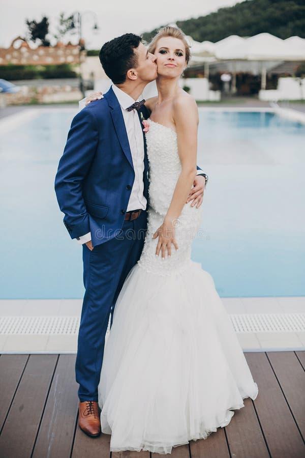 Novia elegante y novio felices que se besan en el agua azul de la piscina en la recepción nupcial en restaurante Pares magníficos imágenes de archivo libres de regalías