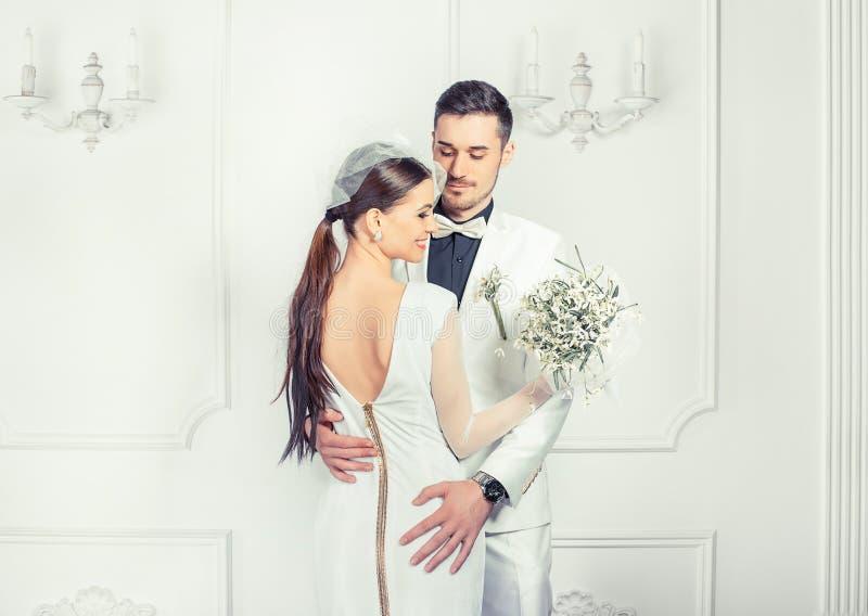 Novia elegante y novio que abrazan sensual imagen de archivo