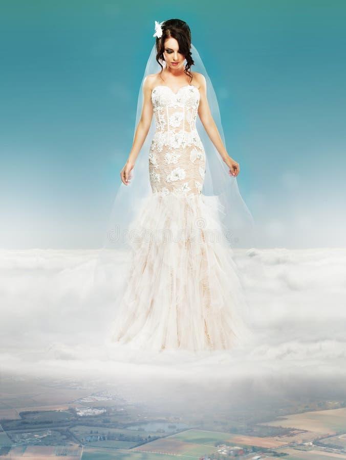 Novia en casarse el vestido blanco que se coloca en una nube imagen de archivo