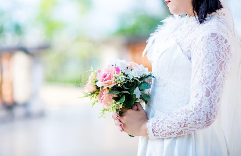 Novia en el vestido blanco de la novia que sostiene el ramo hermoso fresco de la flor en su mano con el fondo de la falta de defi fotografía de archivo libre de regalías