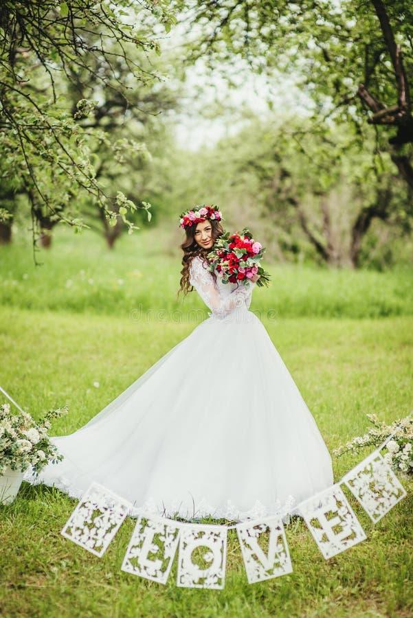 Novia en el vestido blanco en un jardín imagenes de archivo