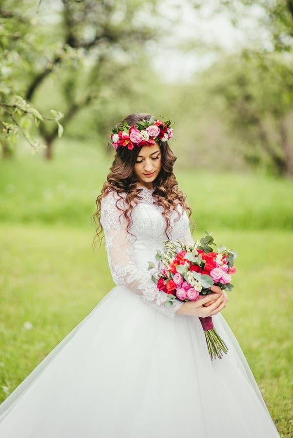 Novia en el vestido blanco en un jardín foto de archivo