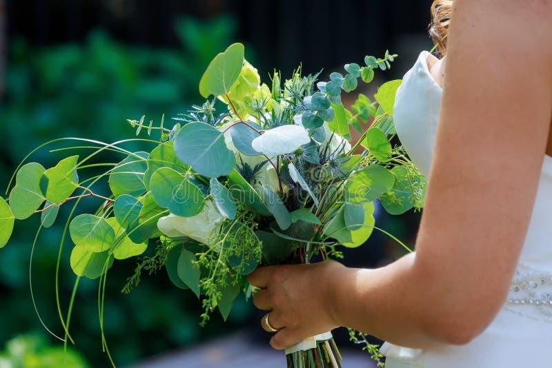 Novia en el vestido blanco que lleva a cabo en el suyo la mano un ramo nupcial de rosas en las flores, casandose fotografía de archivo