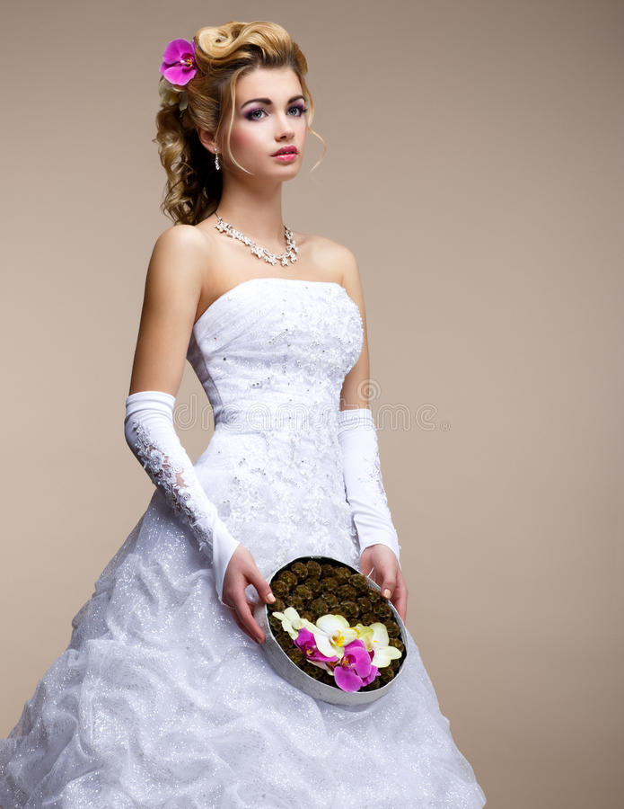 Boda. Blonde de moda de la novia en vestido blanco nupcial y el ramo inusual de flores imagen de archivo libre de regalías