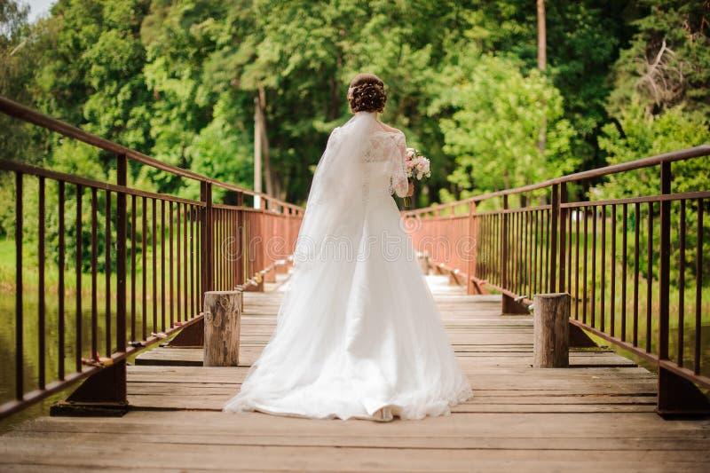 Novia en un vestido blanco largo del cordón que camina en un puente de madera foto de archivo