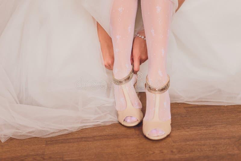 Novia en un vestido de boda hermoso que pone en los zapatos fotografía de archivo libre de regalías