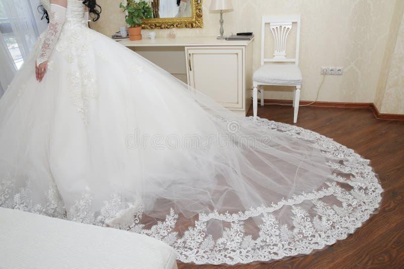 Novia en un vestido que se casa blanco con el cordón y un tren largo foto de archivo