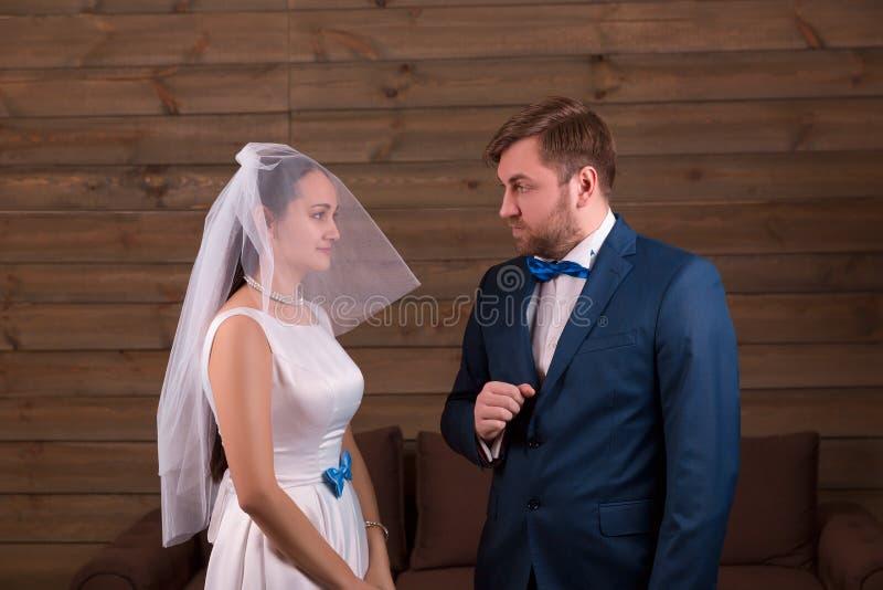 Novia en vestido y velo contra novio en traje fotografía de archivo libre de regalías