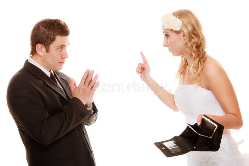 Novia enojada con el monedero vacío y el novio que pelean imagenes de archivo