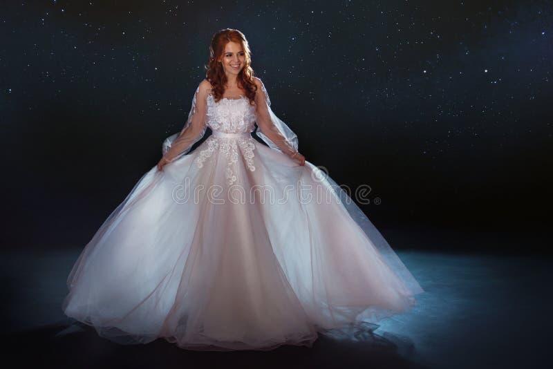 Novia fabulosa en un vestido hermoso entre las estrellas Mujer hermosa joven en vestido de boda con la falda ligera ancha imagen de archivo
