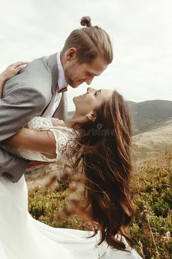 Novia feliz de la tenencia feliz elegante del novio en luz y la sonrisa del sol imagenes de archivo
