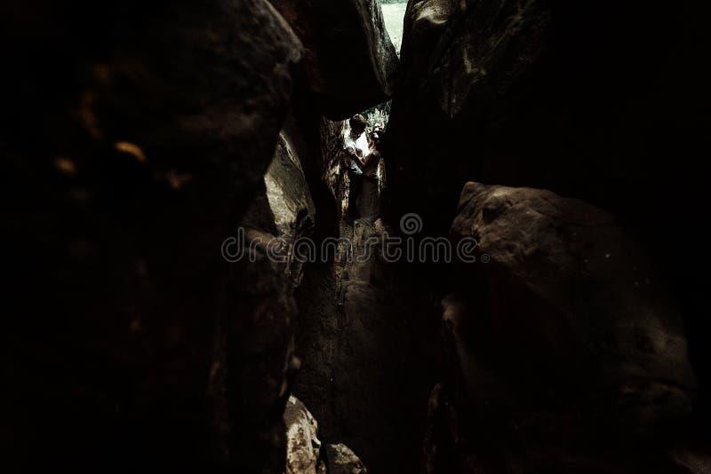 Novia feliz de lujo y novio elegante que se colocan debajo de la roca, unusua fotografía de archivo libre de regalías