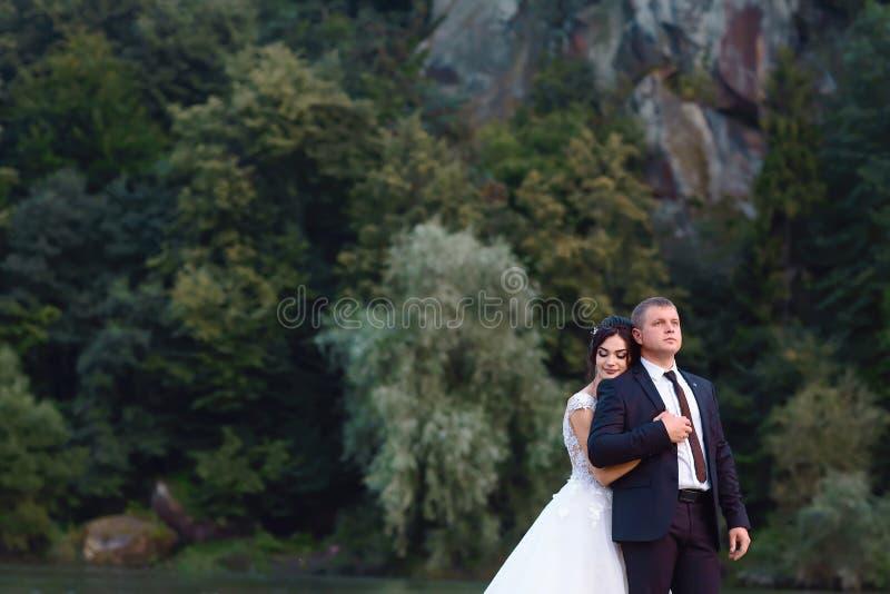 Novia feliz en un vestido blanco elegante y una guirnalda de flores frescas en la cabeza y el novio en las montañas fotos de archivo