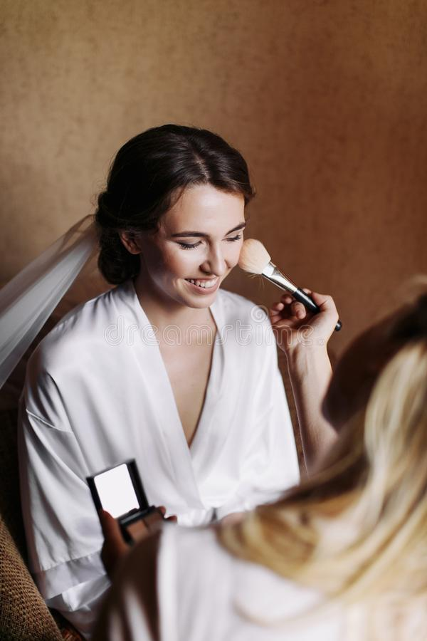 Novia feliz hermosa de la sonrisa con maquillaje de la boda y peinado en el dormitorio, preparación final de la mujer del recién  imagen de archivo libre de regalías