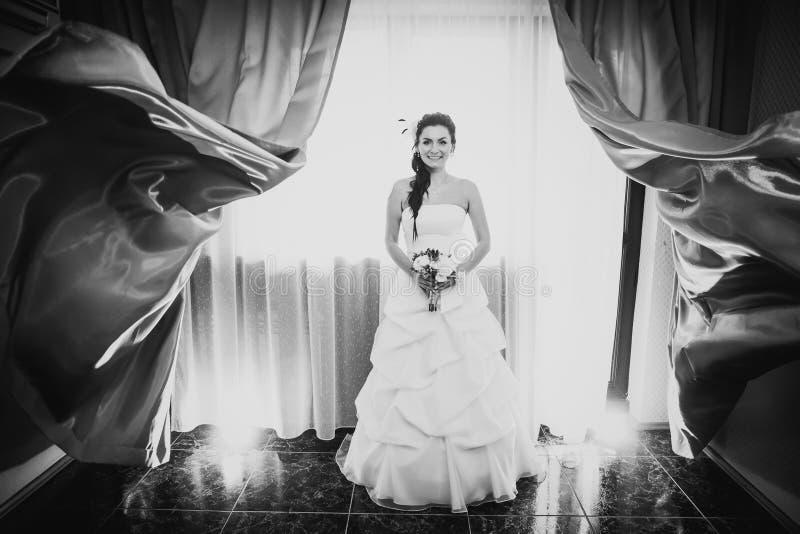 Novia feliz joven hermosa de la fotografía blanca negra que se coloca cerca de la ventana fotos de archivo libres de regalías