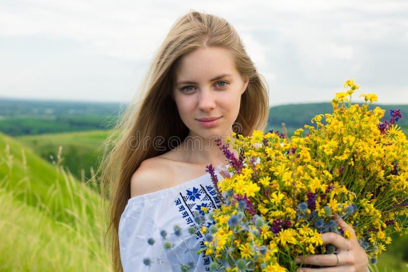 Novia feliz joven que sostiene el ramo de flores amarillas florecientes en campo Imagen de la muchacha feliz hermosa con el pelo  imagen de archivo