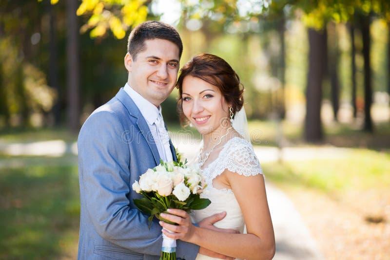 Novia feliz, novio que mira camers en parque verde El besarse, sonriendo, riendo amantes en día de boda Pares jovenes felices en  imagen de archivo