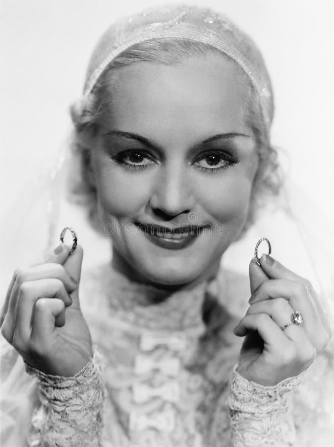 Novia feliz que lleva a cabo los anillos de bodas (todas las personas representadas no son vivas más largo y ningún estado existe fotografía de archivo libre de regalías