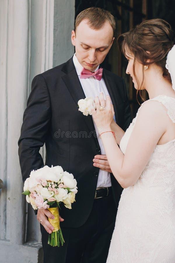 Novia feliz que pone en boutonniere elegante en el traje del novio en las puertas después de ceremonia que se casa en iglesia Par imagen de archivo