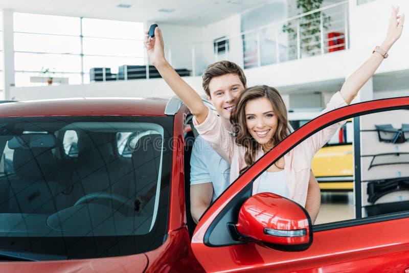 Novia feliz que se coloca con llave y las manos del coche para arriba, novio foto de archivo libre de regalías