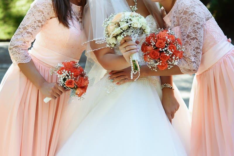 Novia feliz y damas de honor que muestran sus ramos de lujo en Gor fotos de archivo libres de regalías