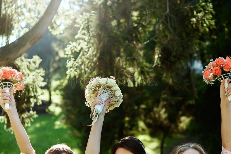 Novia feliz y damas de honor que muestran sus ramos de lujo en Han imagenes de archivo