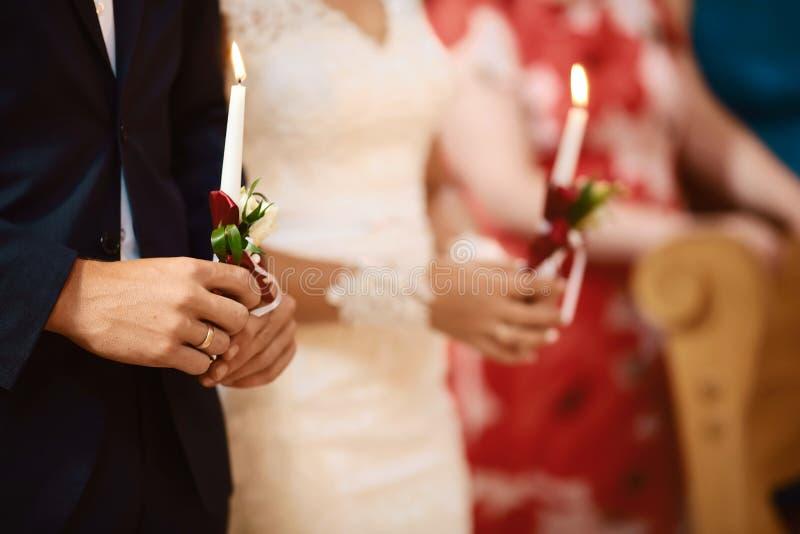 Novia feliz y novio elegante que llevan a cabo la ceremonia de boda de las velas, par de la boda en el matrimonio en iglesia, mom fotografía de archivo libre de regalías
